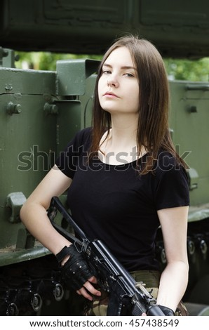 Girl with a gun standing near the armored cars - stock photo
