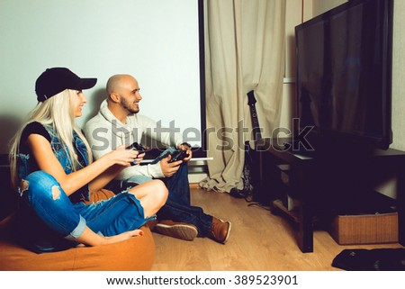 Girl with a guy playing computer games and fun. concept of leisure entertainment and fun - stock photo