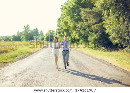 Girl with a guy running down the road holding hands.