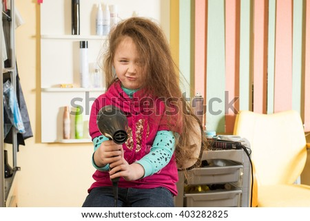 girl with a hairdryer at the barbershop - stock photo