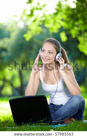 Girl with a laptop and headphones at the park - stock photo