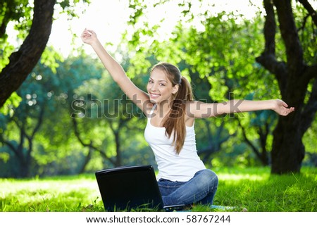 Girl with a laptop in the park with outstretched arms - stock photo