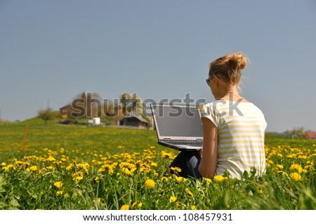 Girl with a laptop on the spring meadow - stock photo