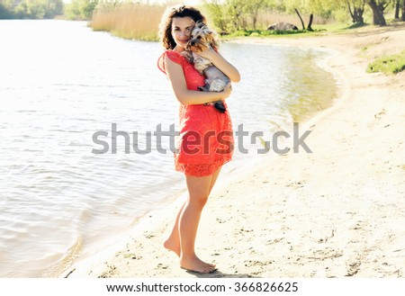 Girl with a little dog on the bank of the river - stock photo