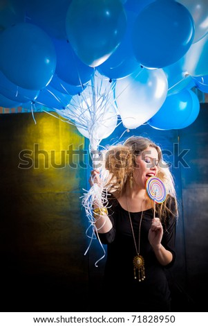 Girl with a lollipop and holding balloons - stock photo