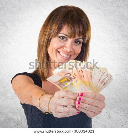 Girl with a lot of money over grey background