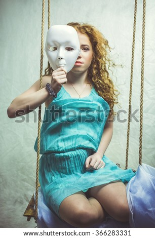 Girl with a mask is sitting on a swing - stock photo