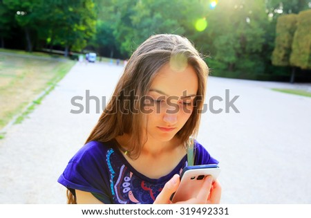 Girl with a mobile phone reads the message in the park - stock photo