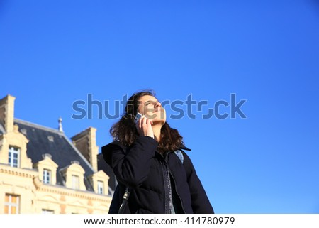 Girl with a mobile phones having fun outside - stock photo
