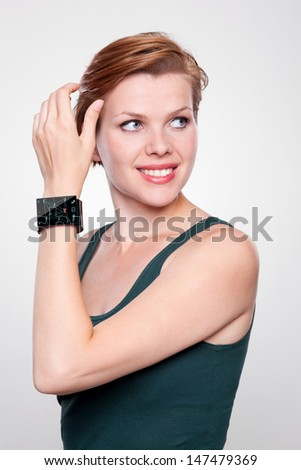 Girl with a modern Internet Smart Watch on grey background. On the screen you can see a symbol for social networks. All Texts, Icons, Interfaces of the Smart Watch where created by myself. - stock photo