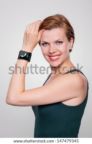 Girl with a modern Internet Smart Watch on grey background. On the screen you can see a symbol of a call. All Texts, Icons, Interfaces of the Smart Watch where created from scratch by myself. - stock photo