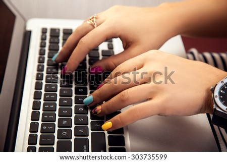 girl with a nice manicure working at a laptop. Worker - stock photo