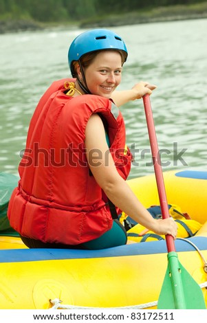 Girl with a paddle on the raft - stock photo