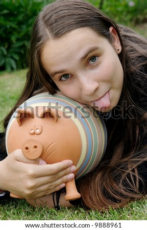 girl with a piggy bank sticking out her tounge - stock photo