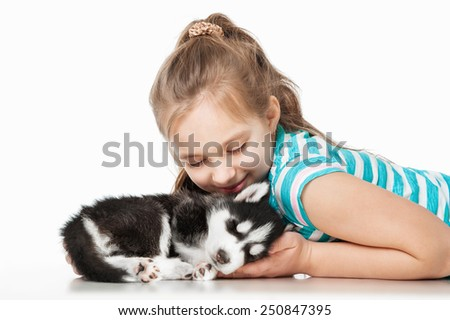 Girl with a puppy husky, on a gray background - stock photo