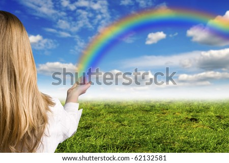 girl with a rainbow raising from her hand - stock photo