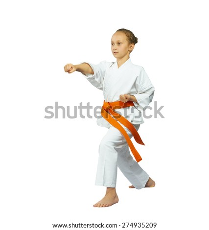 Girl with a red belt in karate position makes punch