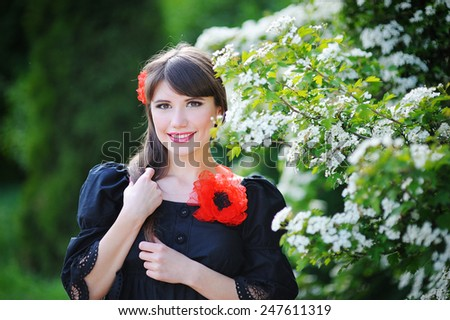 girl with a red bow in the spring flowery park. - stock photo