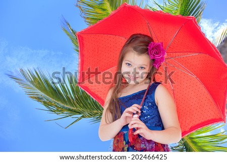 girl with a red umbrella on a background of palm trees.holiday at the seaside,active lifestyle,happiness concept,carefree childhood concept. - stock photo