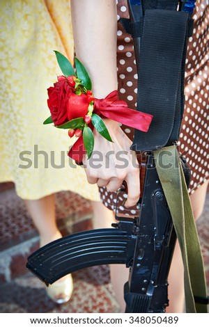 Girl with a rose on her hand holding machine gun - stock photo