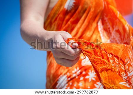 Girl with a shawl in her hands on the beach