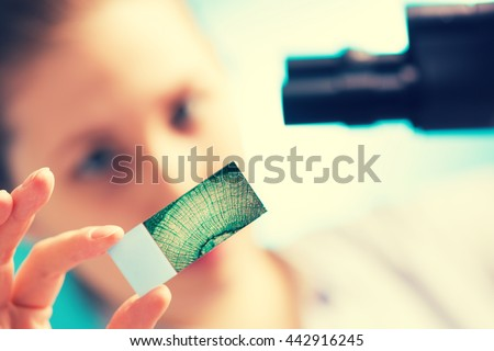 Girl with a slide for the microscope University Hospital - stock photo