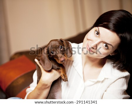 girl with a small dog in the house