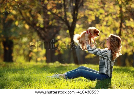 Girl with a small dog in the park Spitz - stock photo