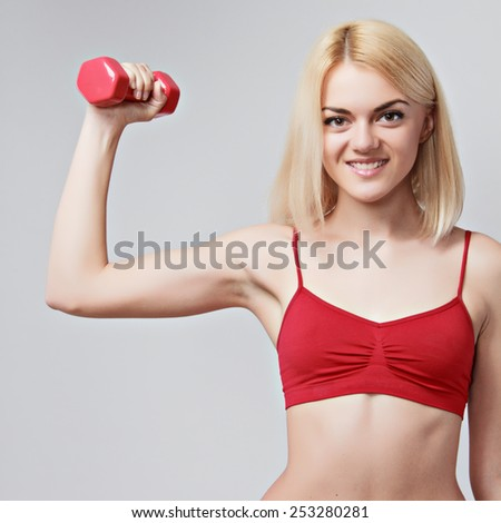girl with a sports figure does exercises with dumbbells on grey background  - stock photo