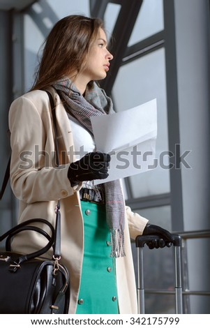 Girl with a suitcase and a bag holding in her hand a letter before the trip - stock photo