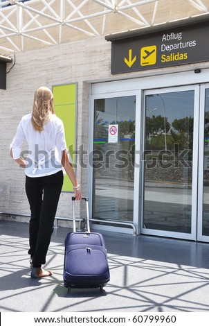 Girl with a suitcase entering airport
