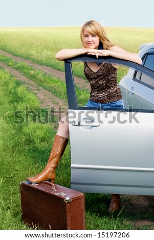 girl with a suitcase near her car - stock photo