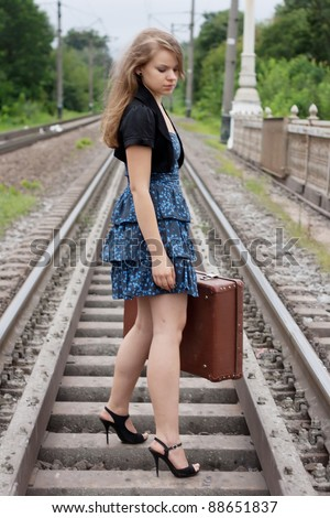 Girl with a suitcase standing on the rails shooting outdoors