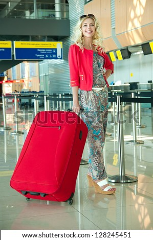 girl with a suitcase walking in the airport - stock photo