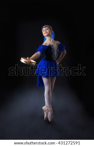 Girl with a tambourine in blue is dancing on a black background - stock photo