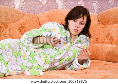 girl with a thermometer and a nasal spray on the couch - stock photo