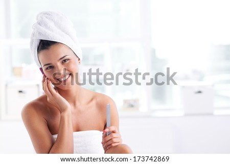 Girl with a towel on her head and body speaking by the phone and looking at camera - stock photo