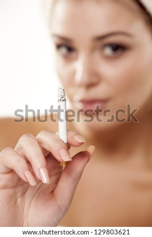 girl with a towel on her head showing her cigarette with focus on foreground