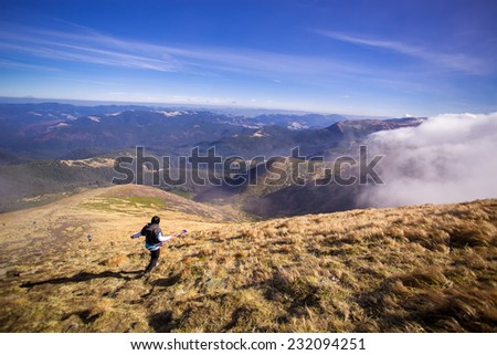 Girl with a travel backpack on the top of a boulder - stock photo