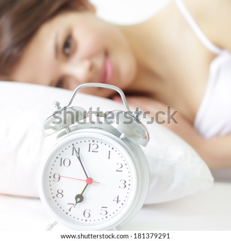 Girl with Alarm Clock on a light background