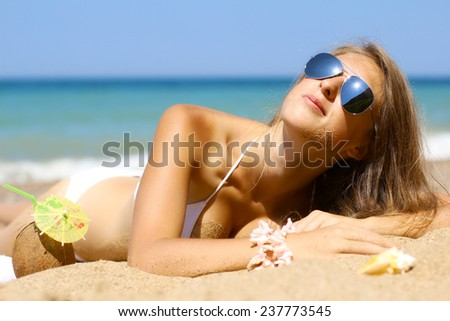 girl with an exotic cocktail posing on the sandy beach