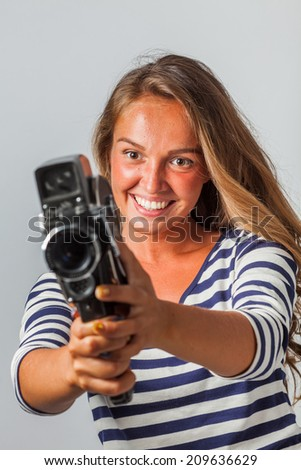 girl with an 8mm retro movie camera - stock photo