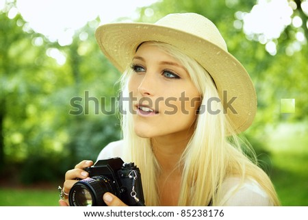 Girl with an old analog camera scouting for subjects. - stock photo