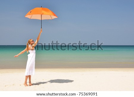 Girl with an orange umbrella on the tropical beach - stock photo