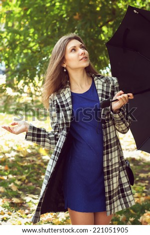 Girl with an umbrella looks whether there is rain - stock photo
