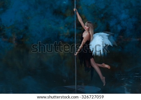 Girl with angel wings circling on a pole dance.  Around her smoke. - stock photo