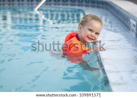 Girl with arm floats holding on to edge of pool - stock photo