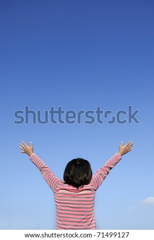 Girl with arms outstretched to the sky - stock photo