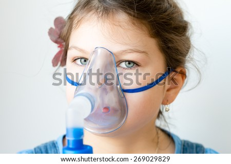 Girl with asthma inhaler. Girl with asthma (or allergy) problems making inhalation with mask on her face. Inhalation treatment of respiratory diseases. - stock photo
