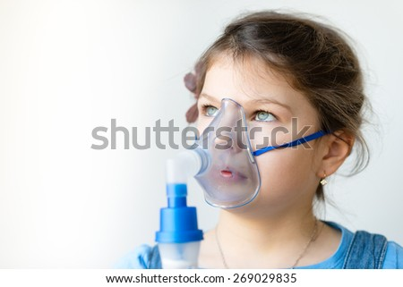 Girl with asthma inhaler. Girl with asthma (or allergy) problems making inhalation with mask on her face. Inhalation treatment of respiratory diseases. Shallow depth of field - stock photo
